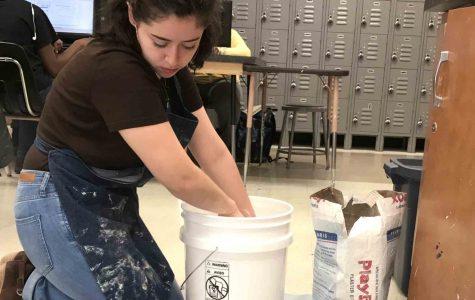 Sarah mixes plaster for her next sculpture.