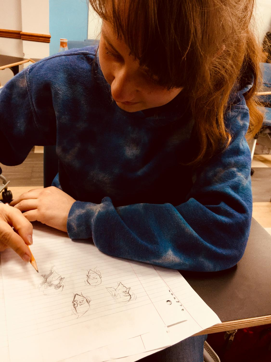 Artistic endeavors Junior Rebecca May (left and right) sketches out faces on a scrap piece of notebook paper. The next edition of EDDA comes out towards the end of April.