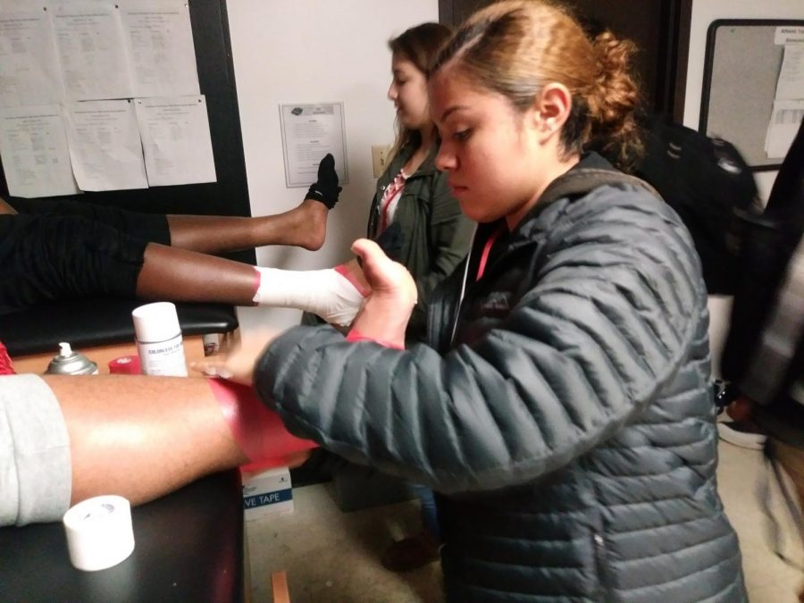 Junior+athletic+trainer+aid+Laura+Zapata+ankle+tapes+junior+offensive+lineman+Denzel+Bryant+before+practice.