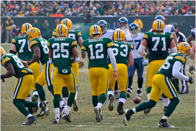 %22Quarterback+Aaron+Rodgers+%2812%29+and+the+Packers+break+the+huddle.%22+by+Mike+Morbeck+is+licensed+under+CC+BY-SA+2.0