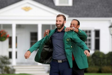Dustin Johnson (left) receives his Green Jacket from former 5-time Masters Champion Tiger Woods (right).