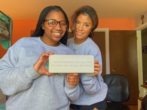 "Sline (right) and Nottke (left) pose with a sign that reads, ""I want every girl to know that her voice can change the world."" The pair is also wearing their (f)embolden embroidered crewnecks."