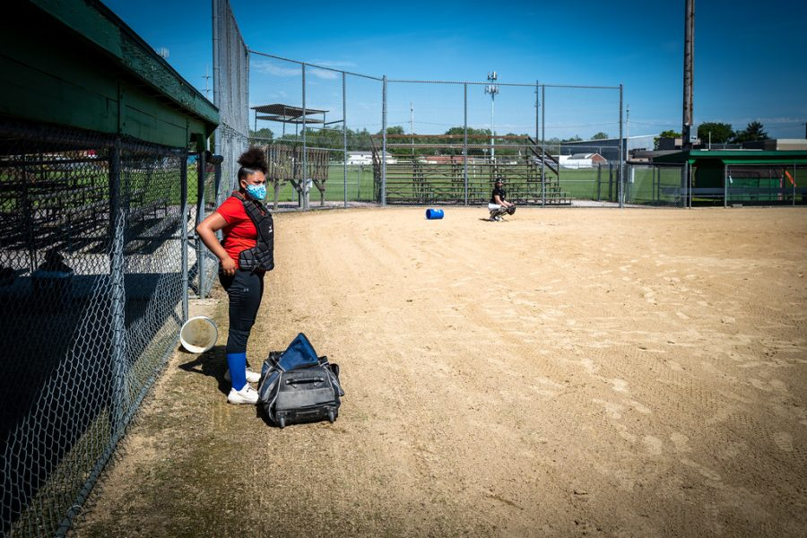 Two softball players look to be preparing for the season in a remote setting.